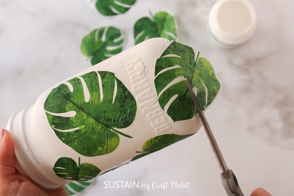 Placing the leaf cut out over top of the glue on the glass jar.