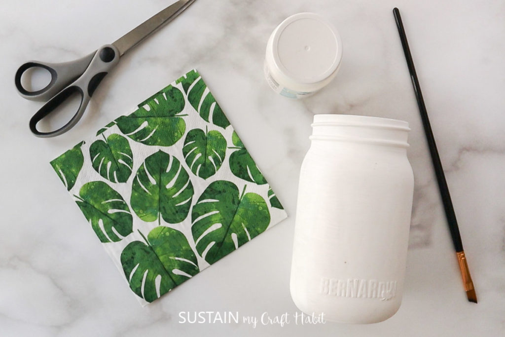 Materials needed to decoupage napkins onto glass jars, including napkins, glass jars, paint, paint brush and scissors.