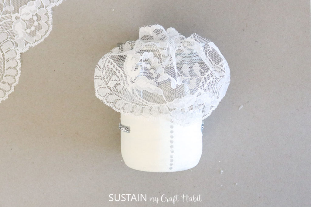 Adding lace fabric to the top of the jar.