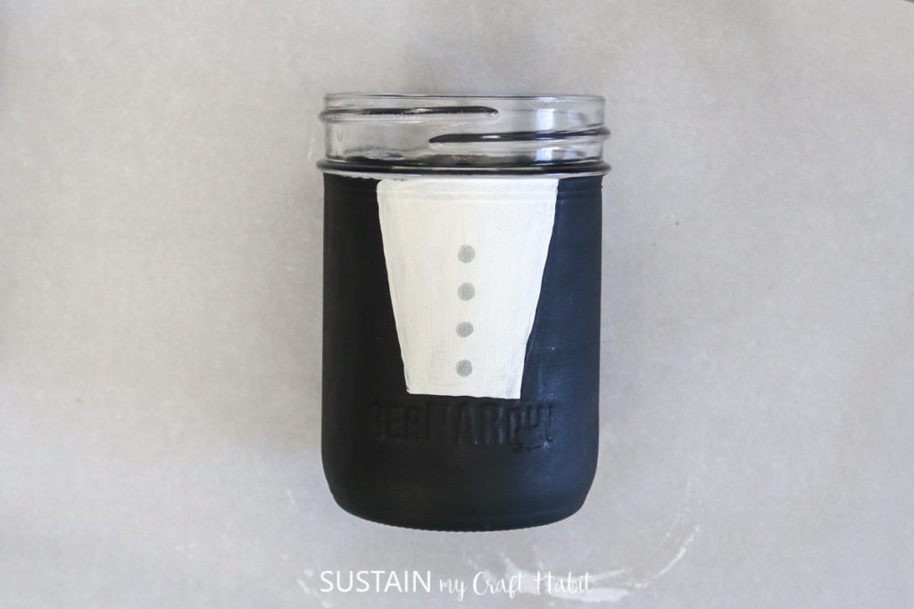 Using silver paint to dab buttons onto the groom glass jar.