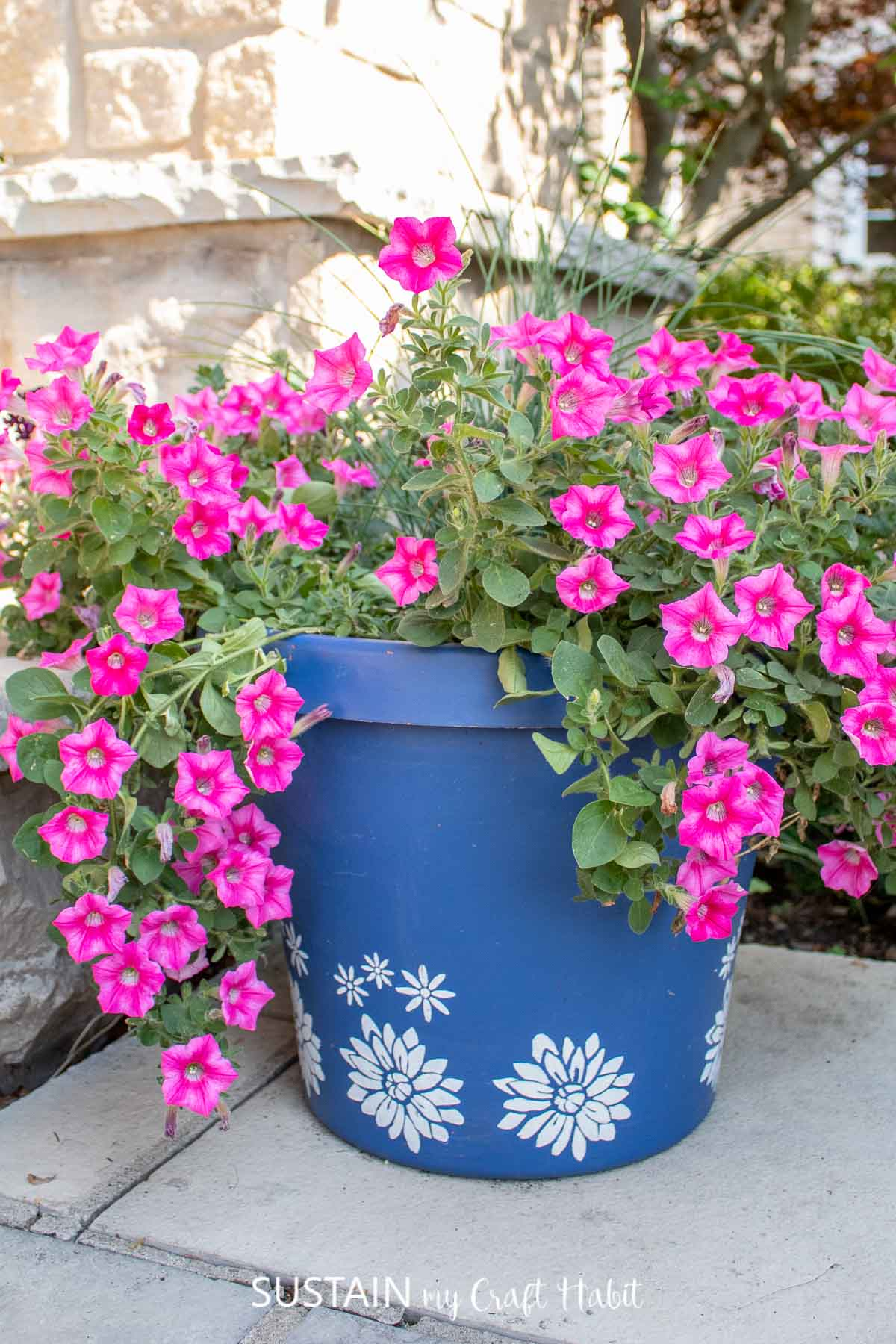 A bright blue planter with white stenciled flowers. They planter is overflowing with fresh pink flowers.