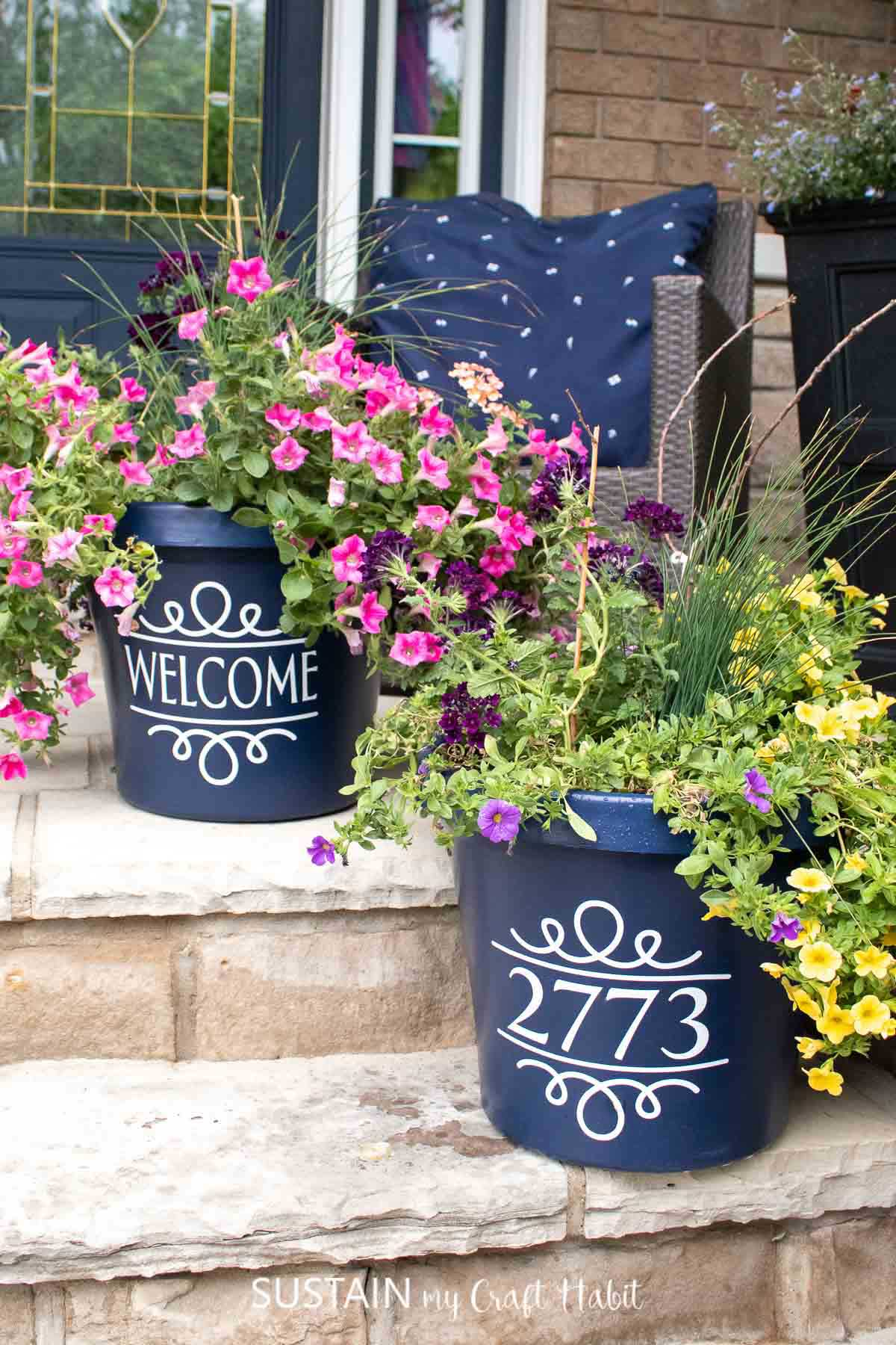 A pair of navy blue planters staggered on the steps of the porch. The planters are filled with colorful flowers and have white decals on the front. One decal says welcome and the other has a house number.