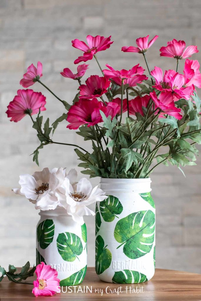 Napkin decoupage on glass jars filled with flowers.