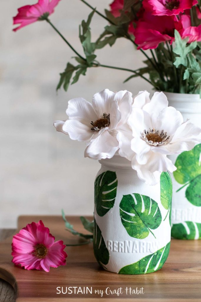Finished glass jar with napkin decoupage filled with white flowers.