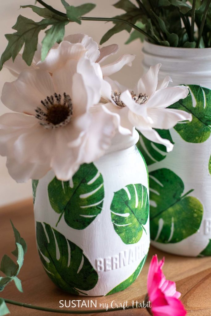 Close up of leaf napkin decoupage on glass jars filled with flowers.