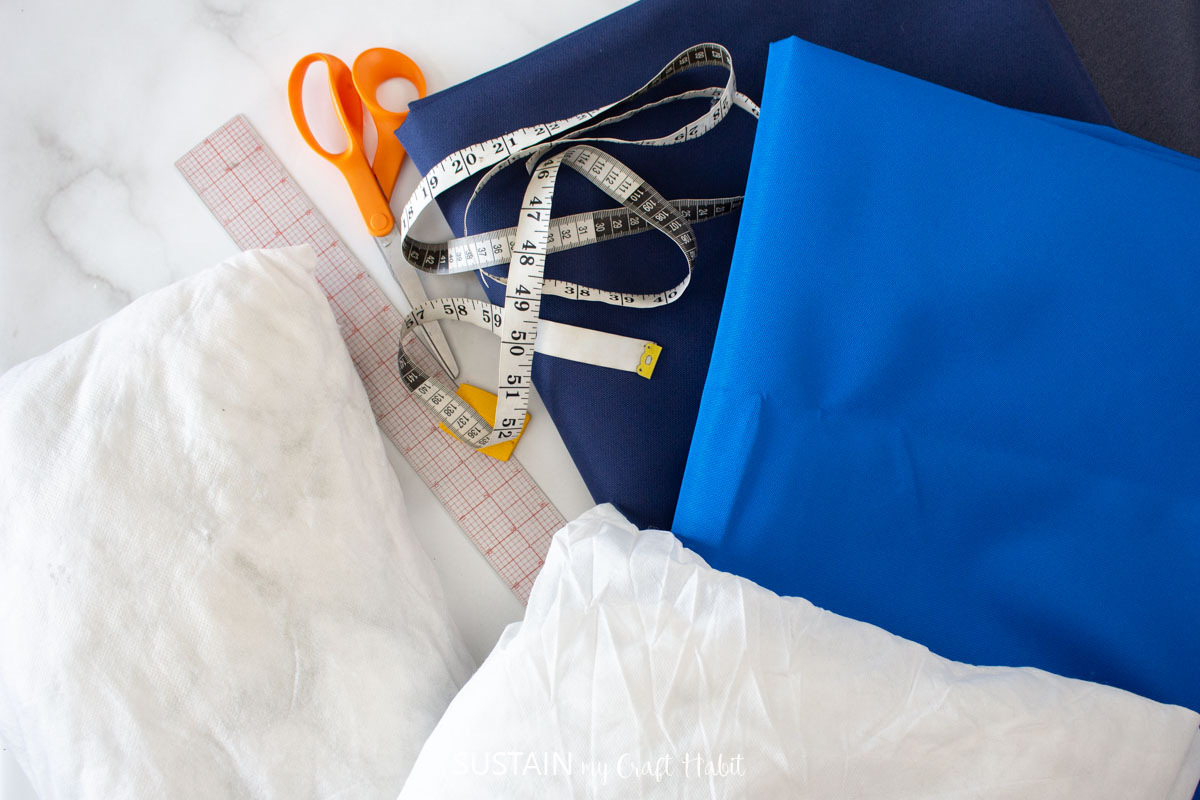 Materials needed to make outdoor pillows including fabric, scissors, pillows, and ruler.