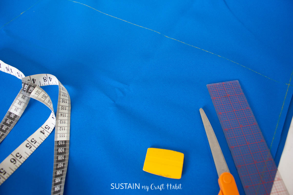 Measuring and marking blue fabric.