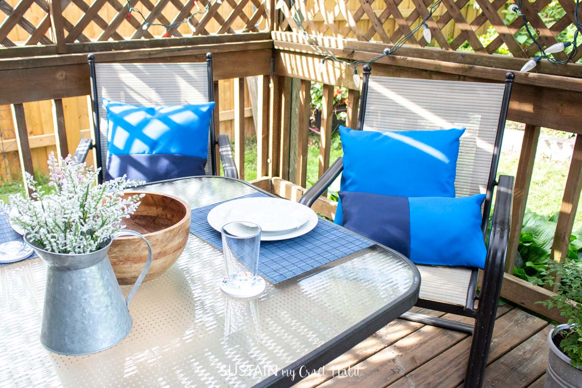 Blue outdoor pillows on chairs on a deck.