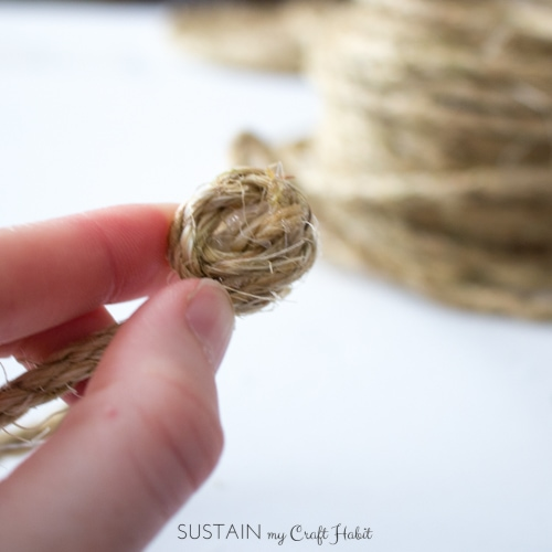Adding a dab of hot glue to the end of sisal rope.