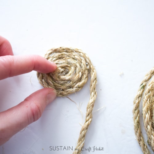 Adding hot glue and wrapping the sisal rope around itself.