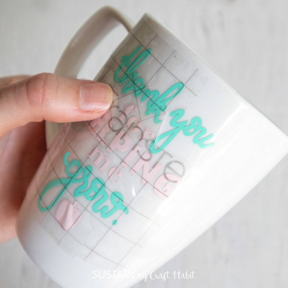 Pressing down the transfer tape and phrase onto a coffee mug.