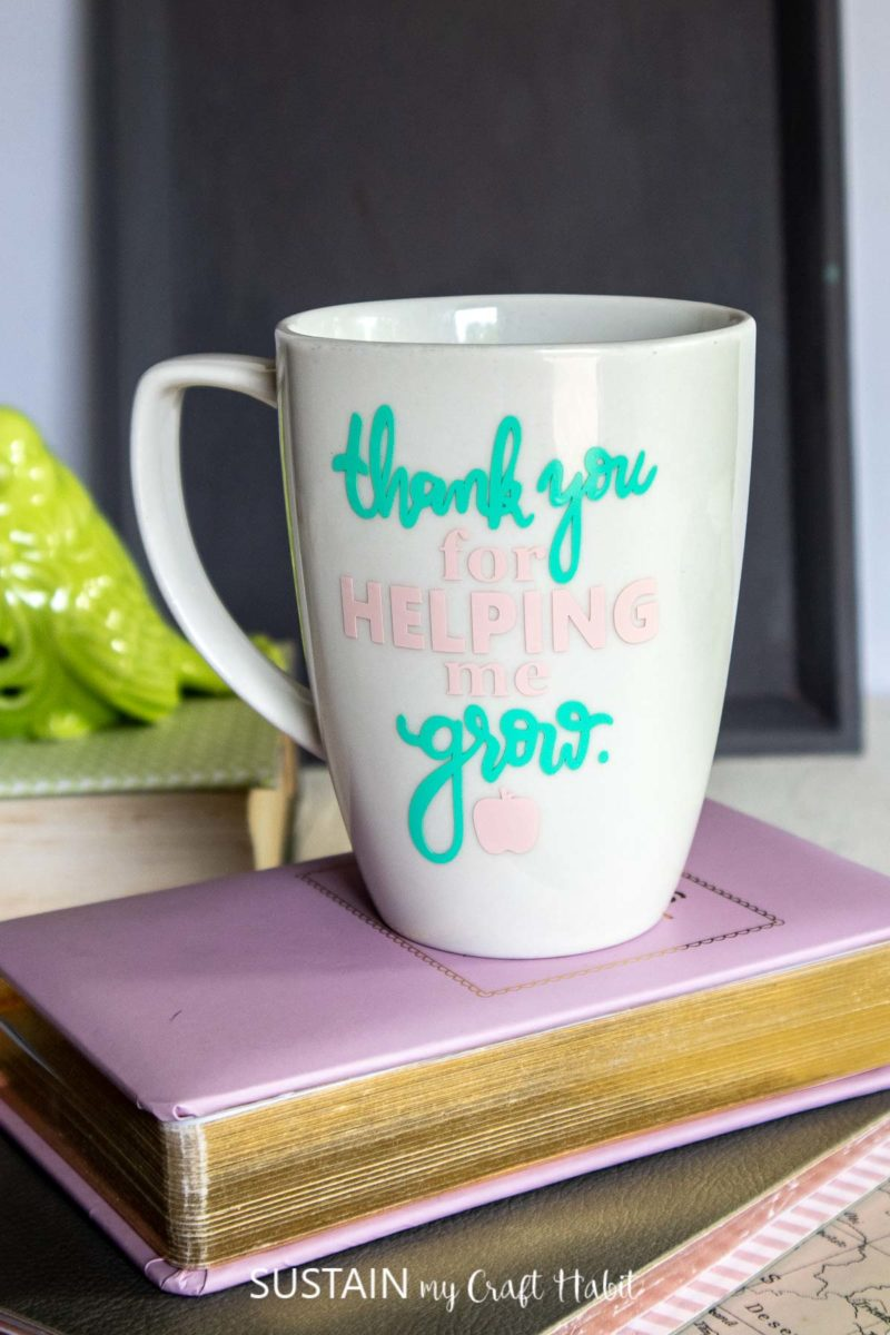 """Coffee mug for teachers with """"thank you for helping me grow"""" phrase on the front and placed on top of a purple book."""