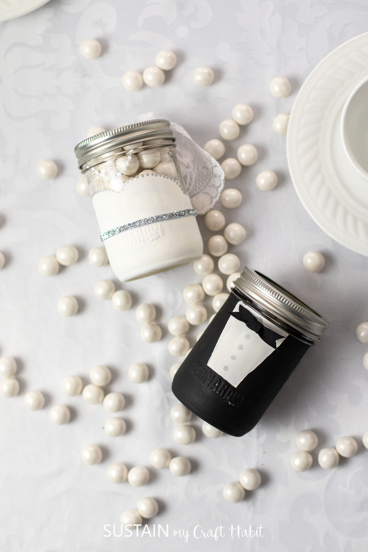 Bride and groom glass jar wedding favors laid on a table next to candy.