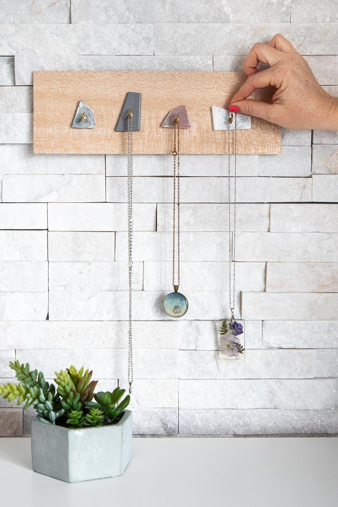 Modern jewelry display with faux resin marble hooks.