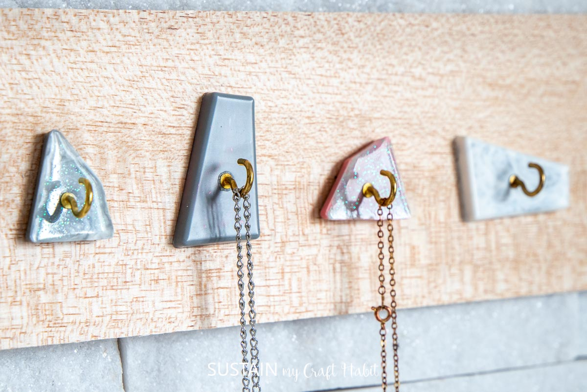 Close up of modern jewelry display with faux resin marble hooks.