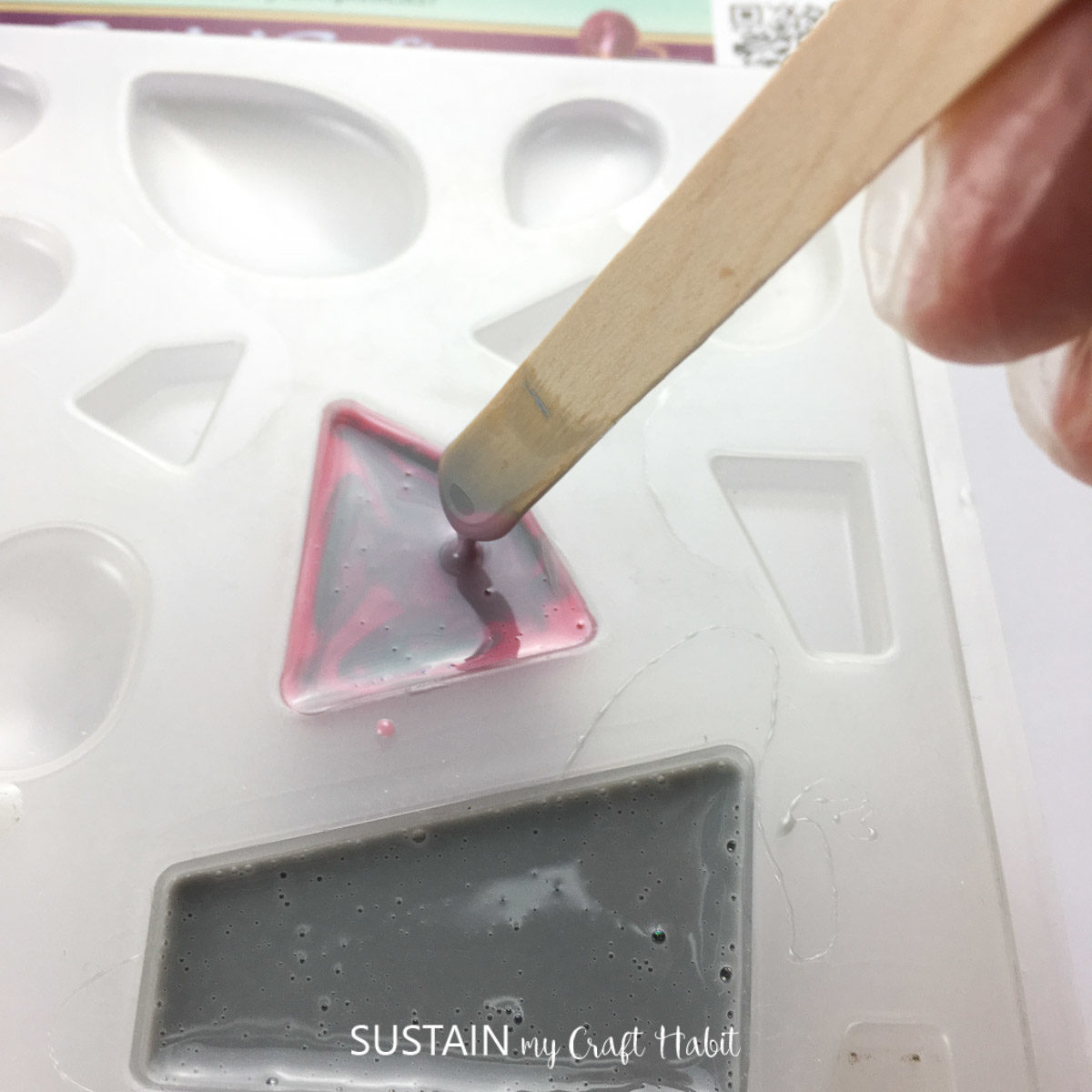 Mixing grey and pink resin in a mold using a wooden stick.