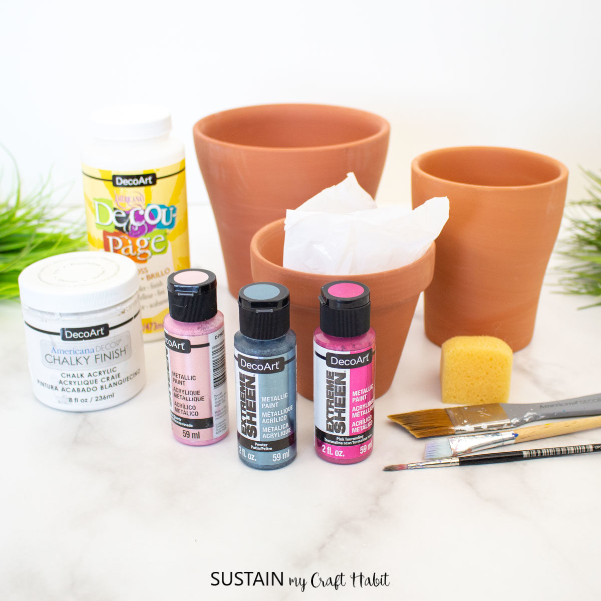 Materials needed to make painted marble effect terracotta pots including clay pots, paint, and paintbrushes.