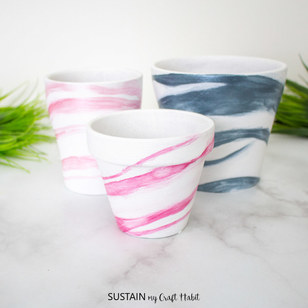 Terracotta pots painted with pink and blue marble effects.