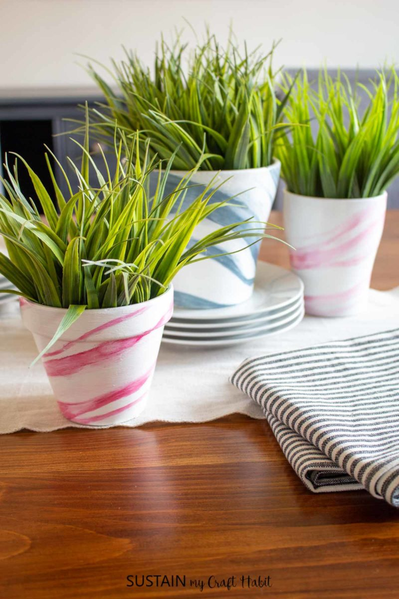 Terracotta pots painted with a marble effect and holding green plants.