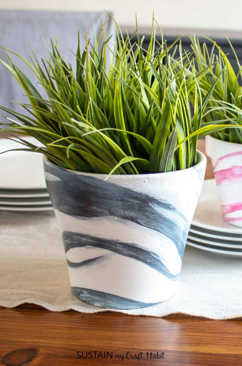 Terracotta pots painted with a blue marble effect and holding green plants.