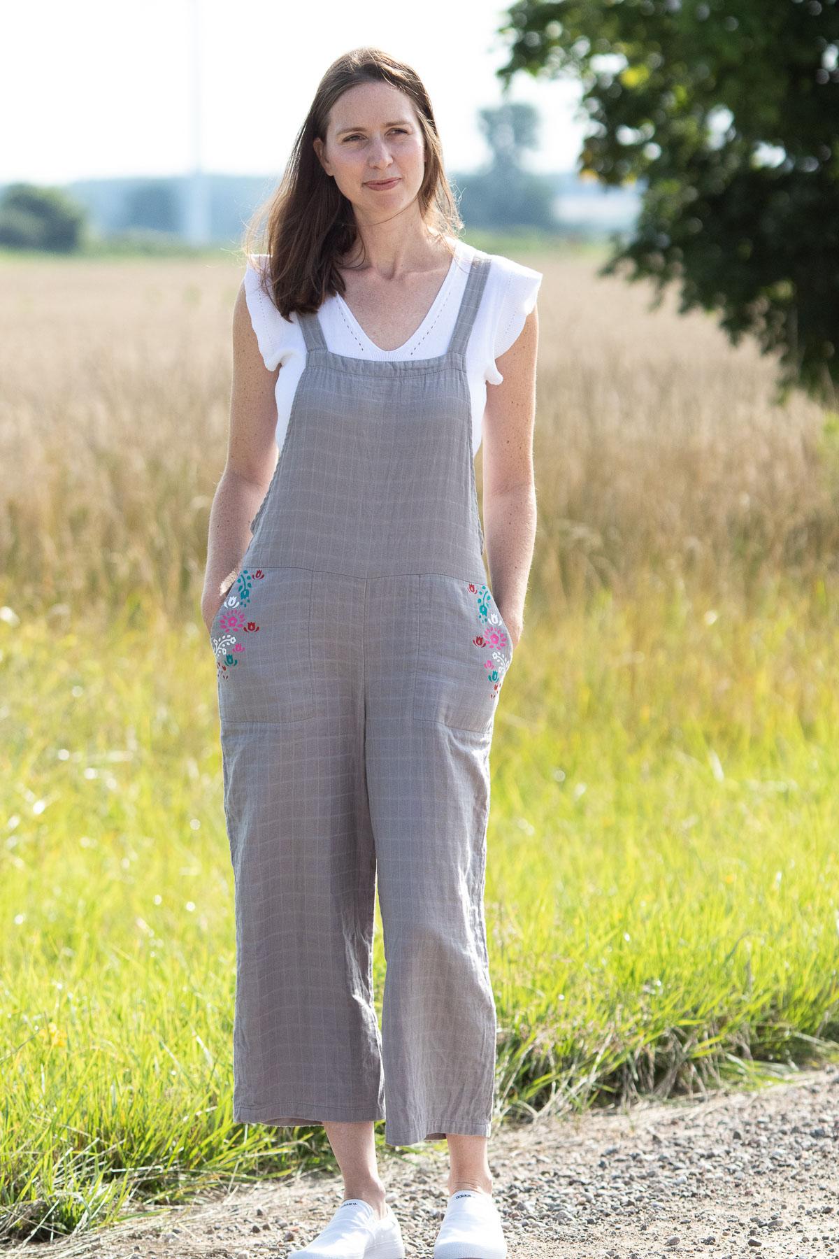 woman wearing jumpsuit standing near farm field