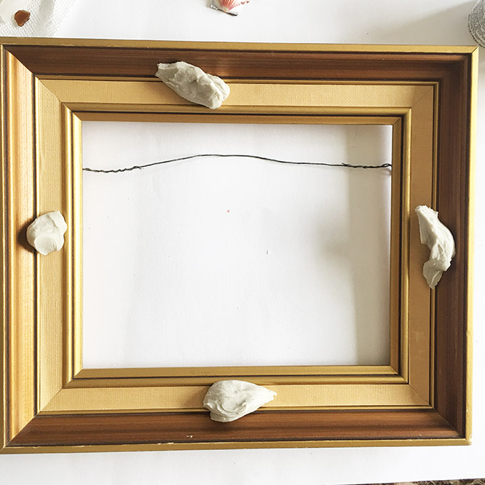 Separating the clay and placing it around the picture frame.