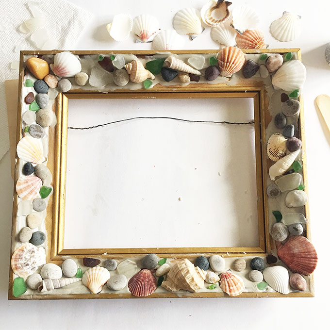Beachcombers picture frame filled with shells, sea glass and pebbles.