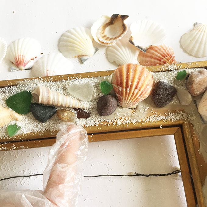 Adding white decorative sand to the picture frame.