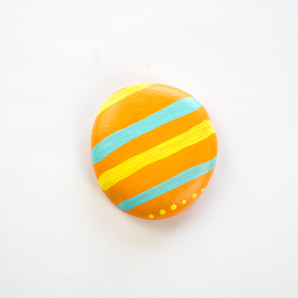 Adding yellow lines and dots to the painted rock.