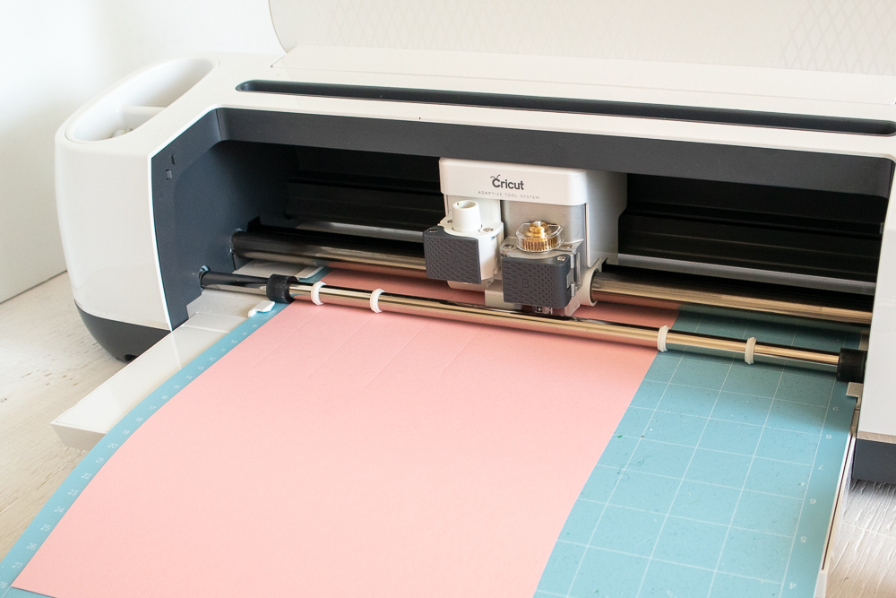 Loading pink cardstock into the Cricut machine.