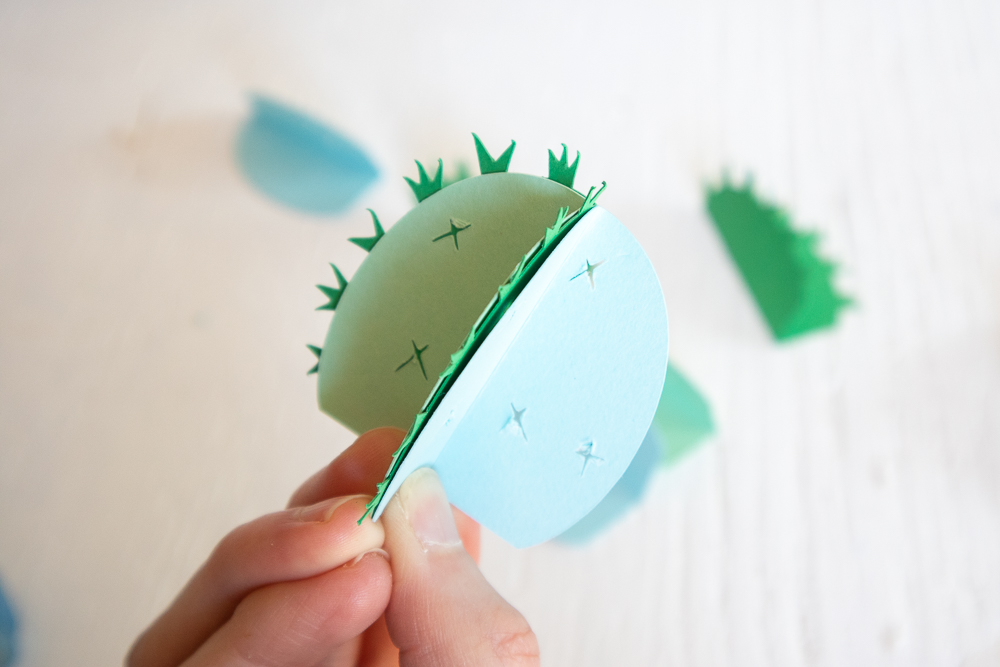 Gluing the folded cardstock together to form the 3D paper cactus.