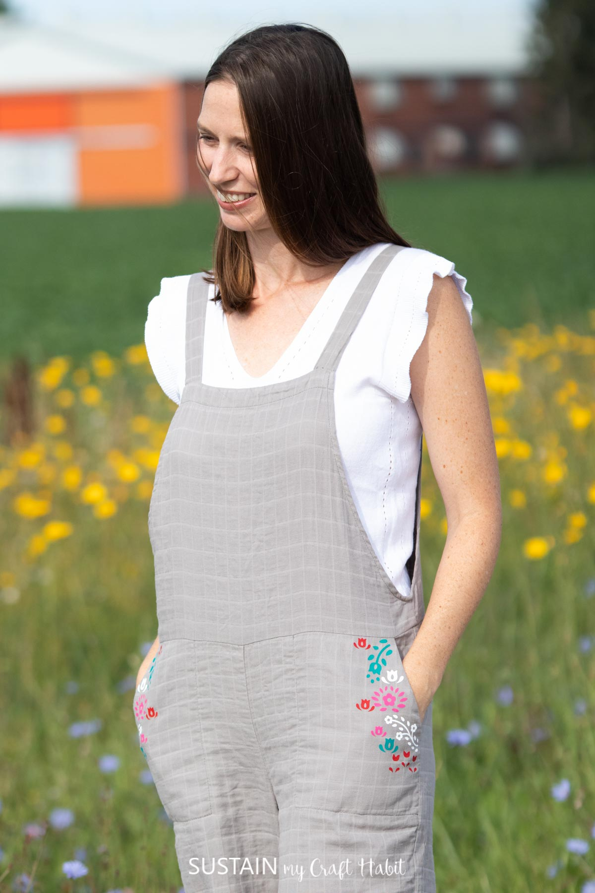 woman smiling with hands in her pockets