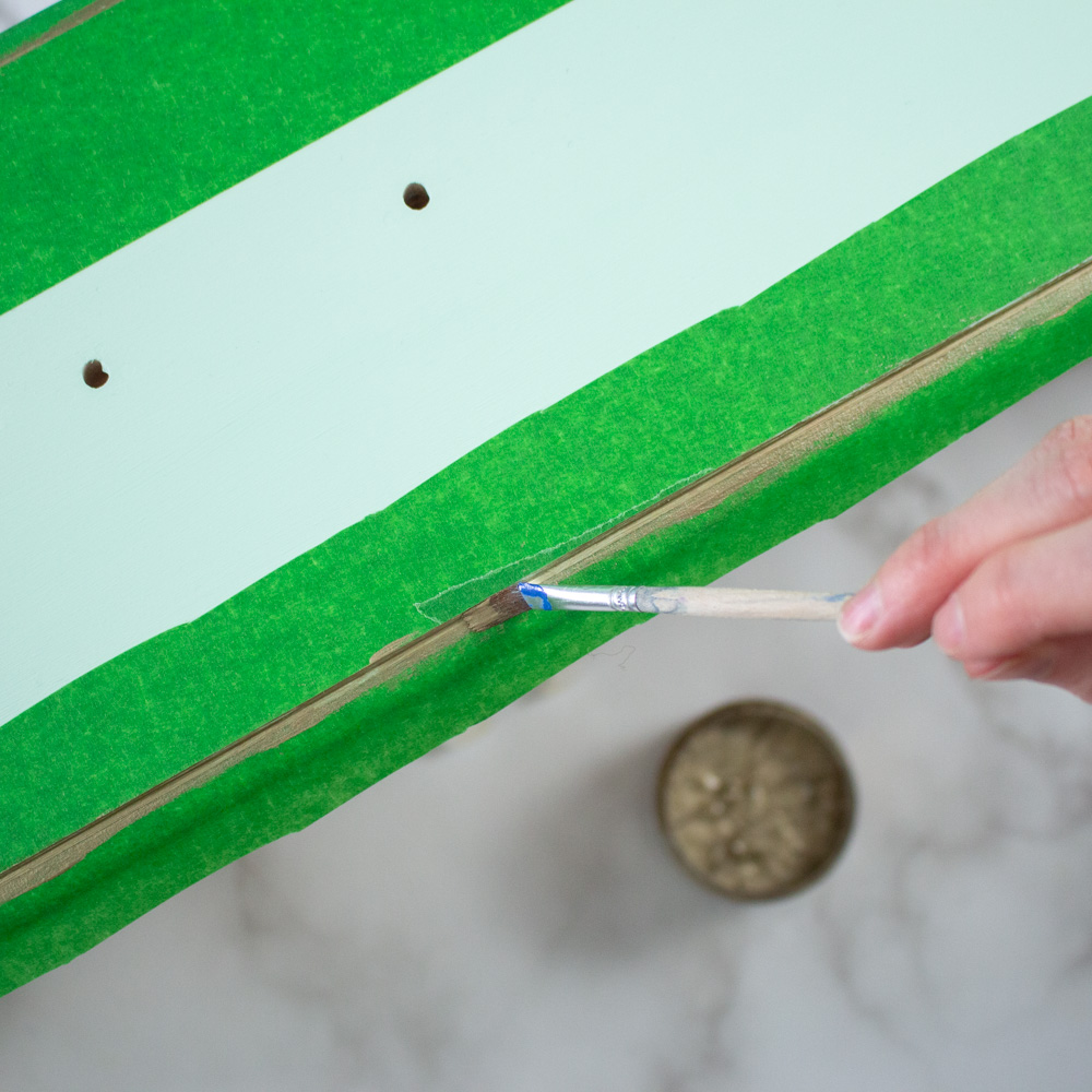 Adding gold detail to the front of the drawer with a fine paint brush.