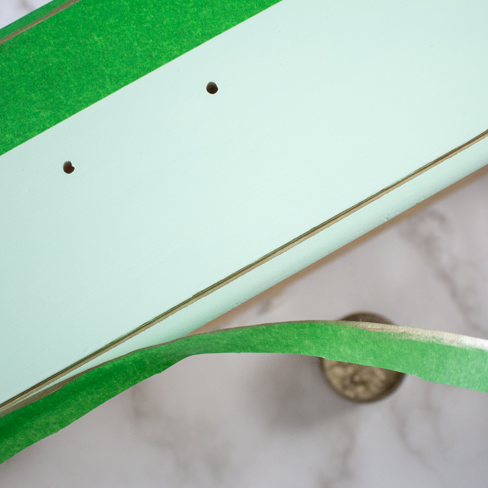 Removing the green painter's tape from the painted dresser drawer to reveal a crisp gold edge of paint.