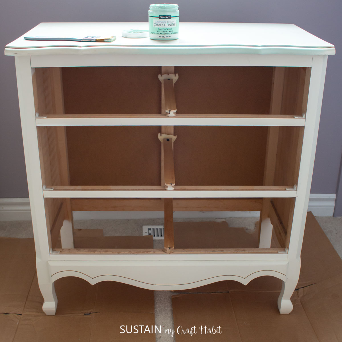 Starting the modern french country furniture makeover by painting the dresser with green paint.