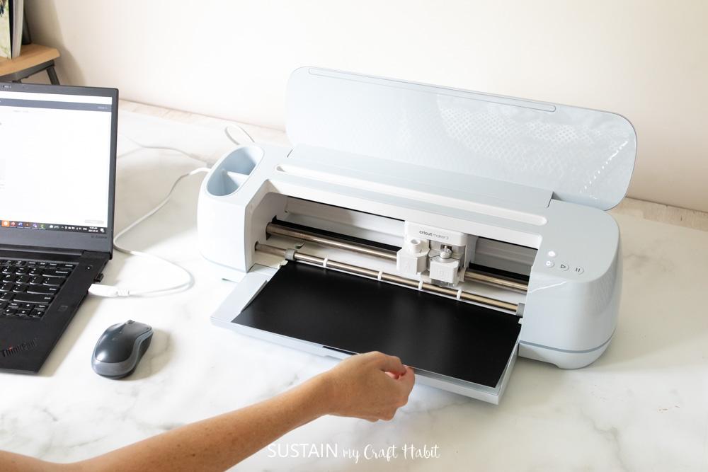 loading the black smart vinyl in to cricut maker 3