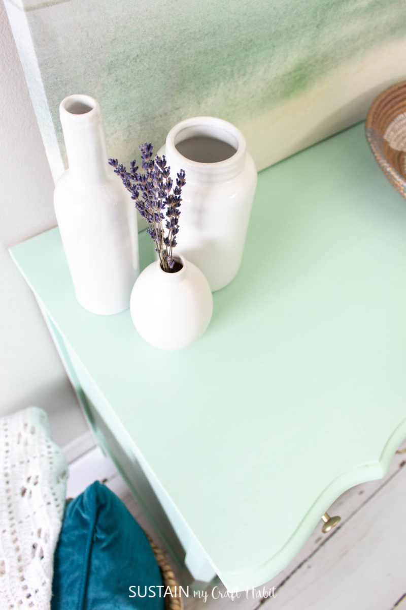 Overhead view of white vase accessories on the mint green painted dresser.