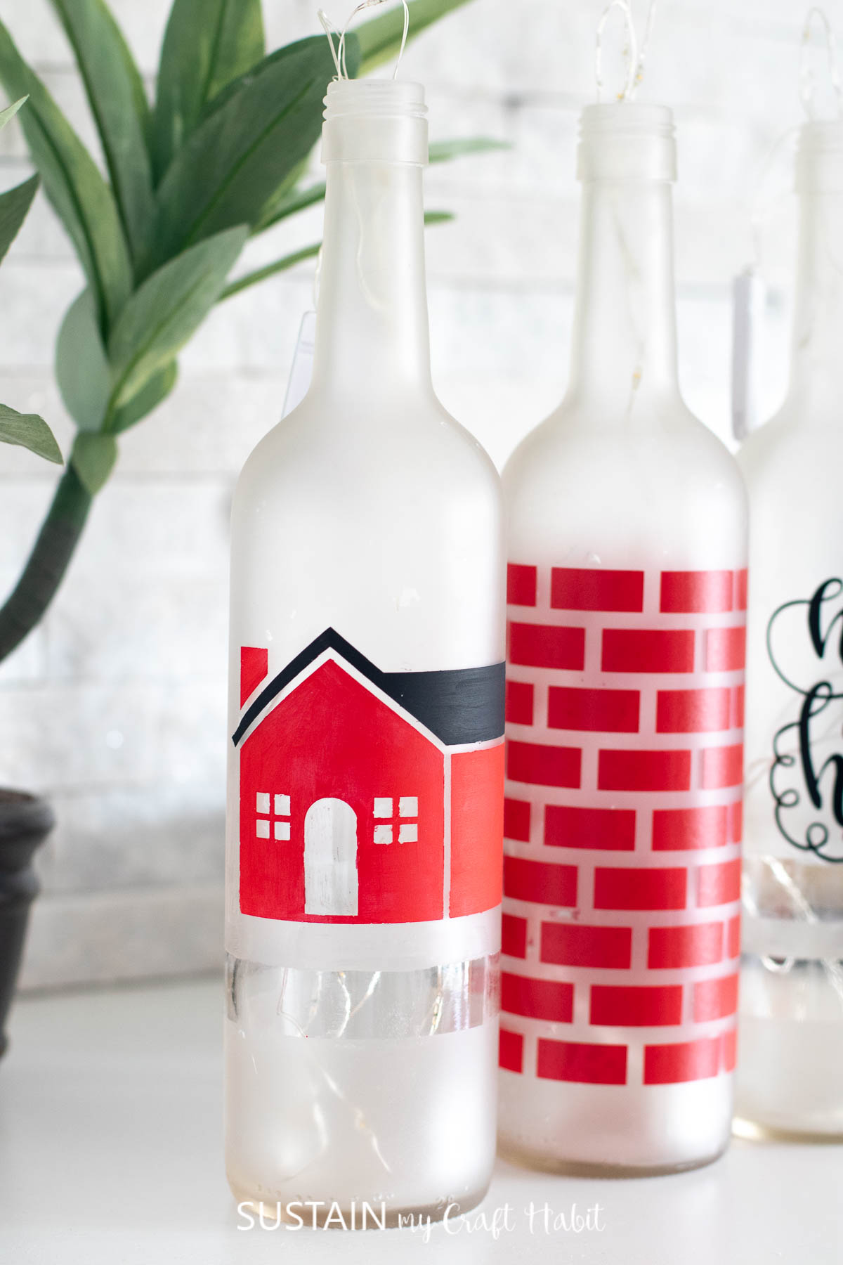 Close up image of the bottle painted with a red and white house using the vinyl stencil cut wiht the Cricut Maker.