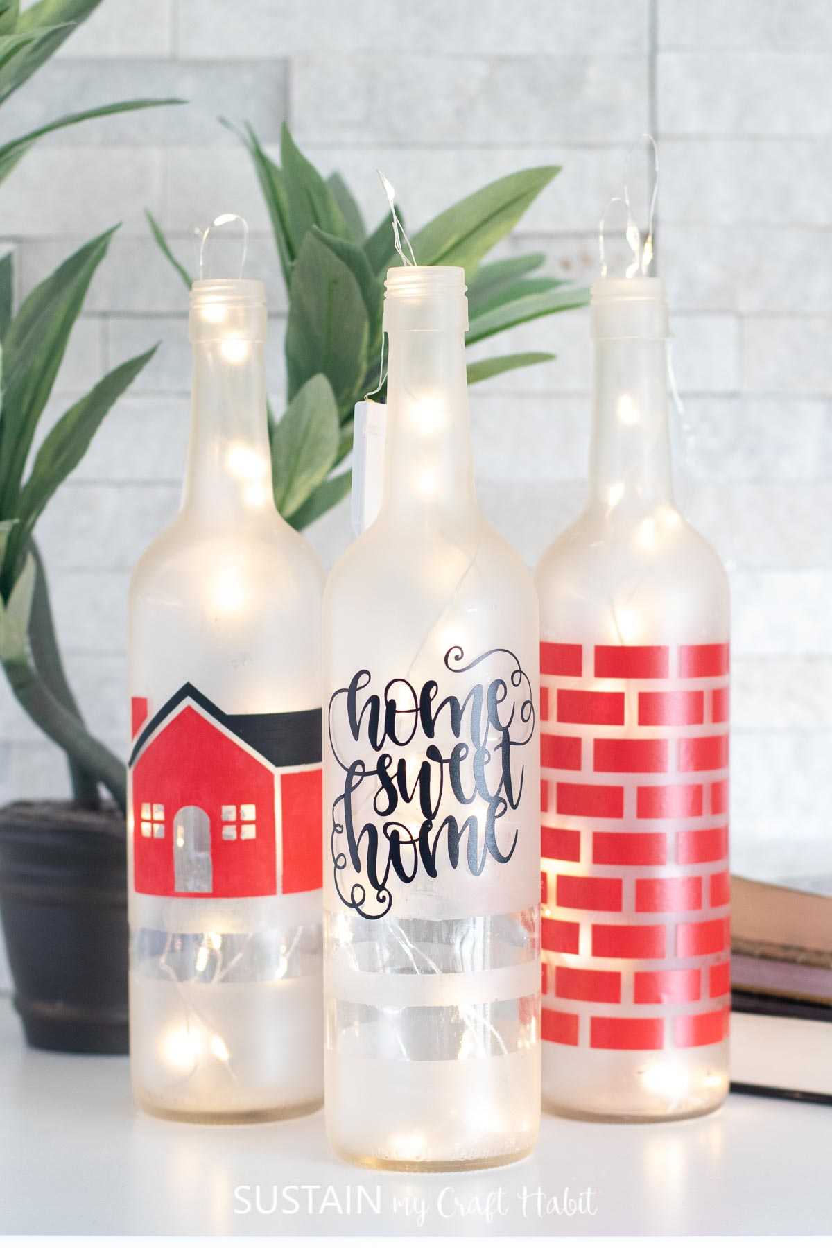 Three completed painted bottles arranged in a cluster on a white surface. Lit twinkle lights are eluminating the frosted bottles.