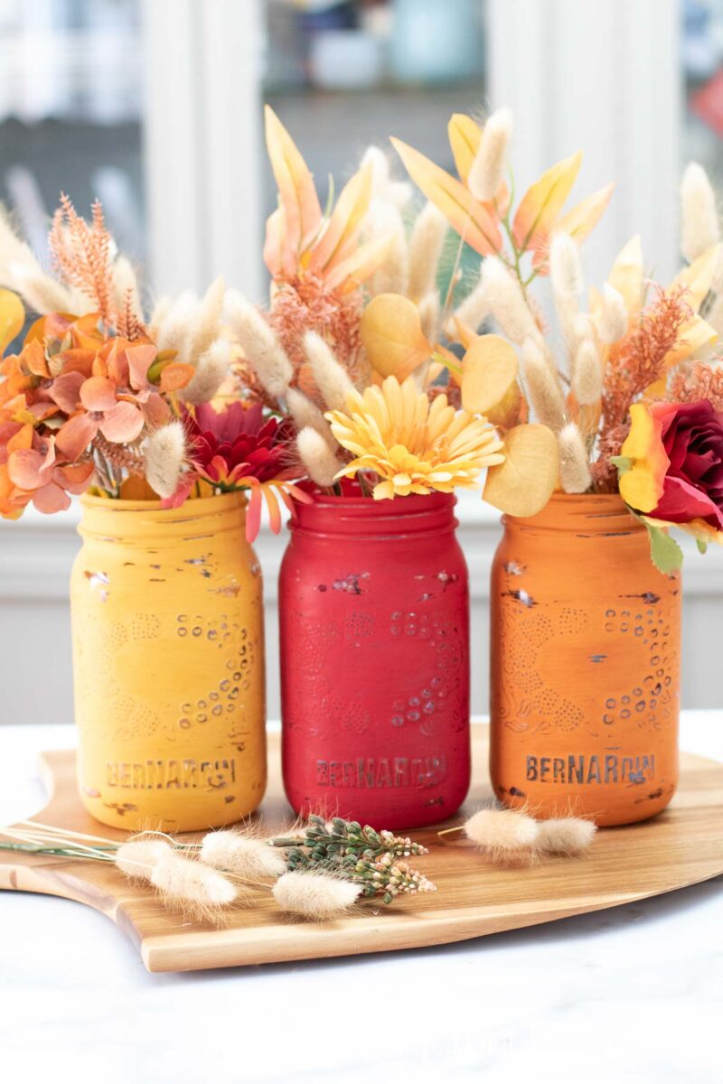Painted jars for Thanksgiving filled with fall flowers and lagurus bunches.