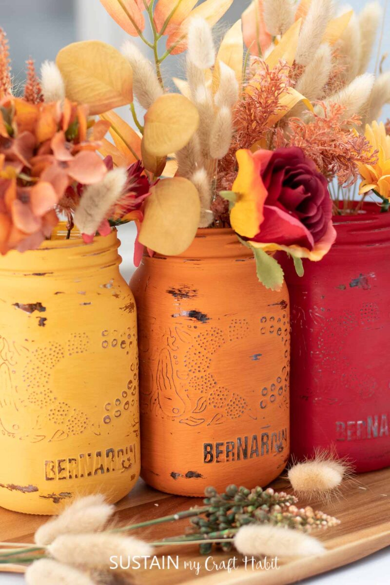 Close up of painted jars for Thanksgiving filled with fall flowers and lagurus bunches.