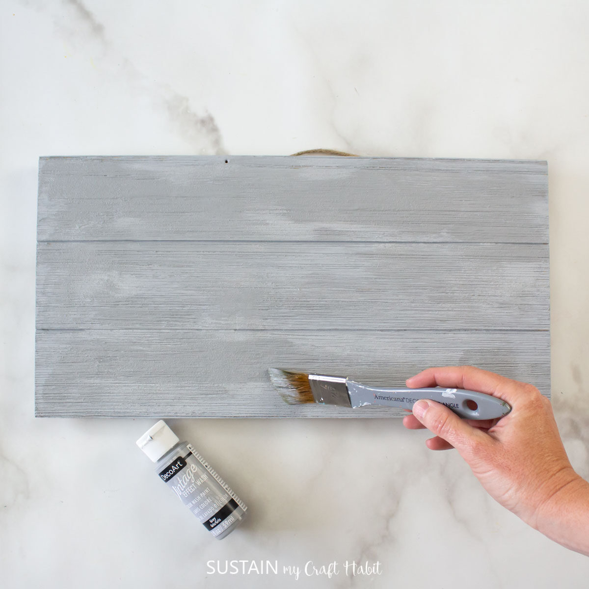 Adding vintage grey paint over the painted pallet wood.