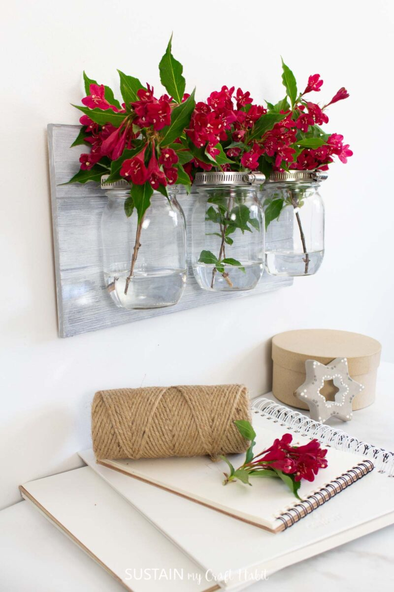 Mason jar wall sconce filled with flowers.