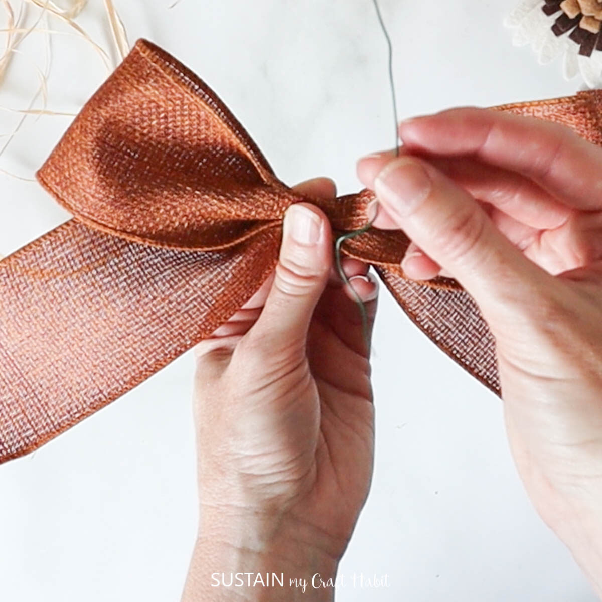 Securing the ribbon bow with floral wire.