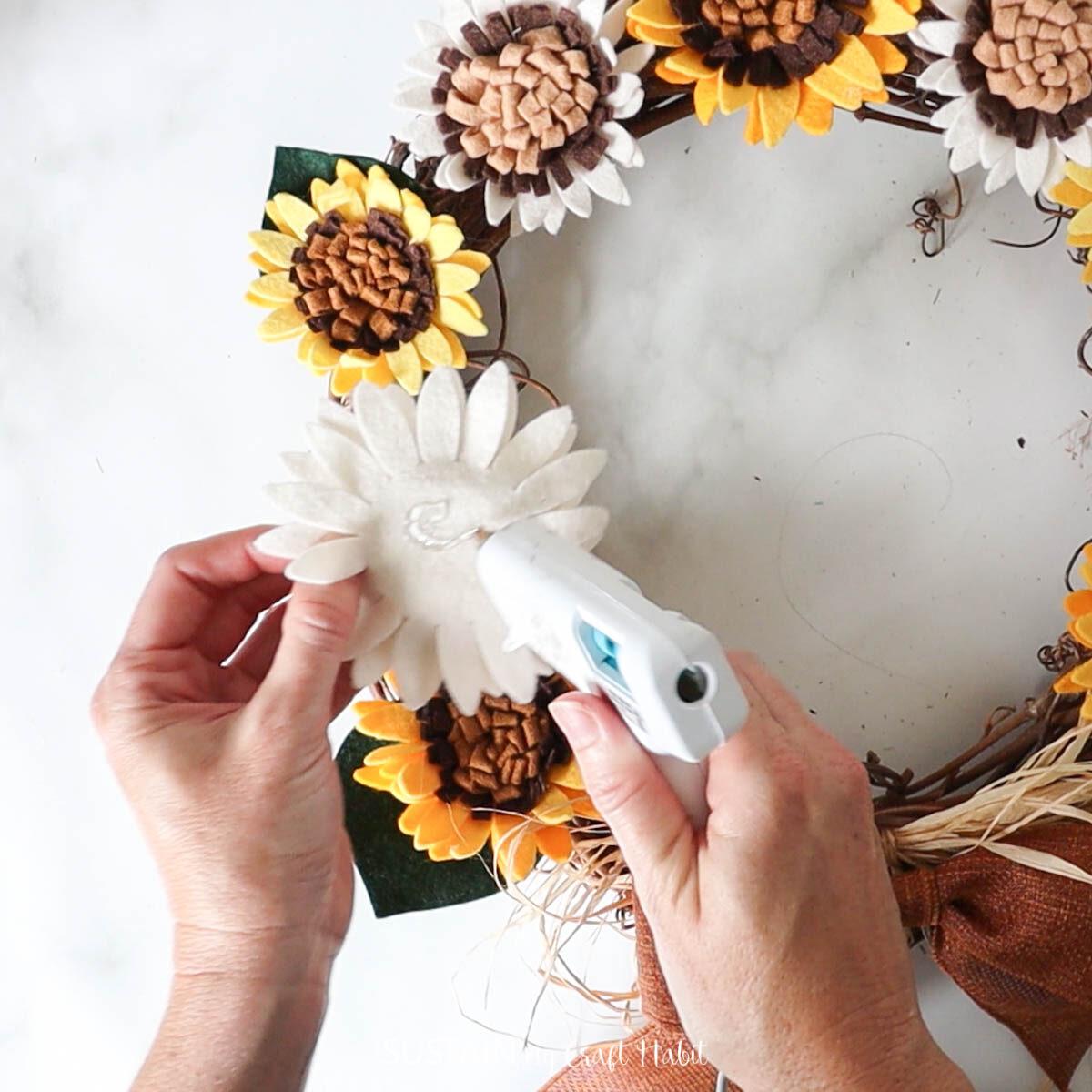 Gluing a felt sunflower onto the wreath.