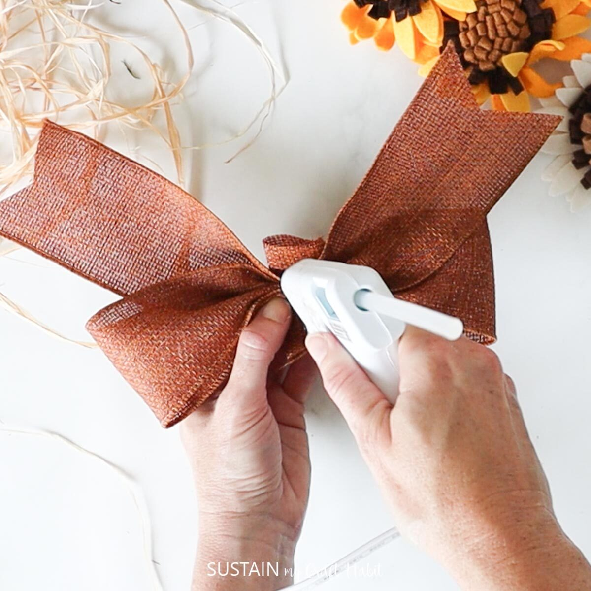 hot gluing a piece of ribbon in the middle of the bow.
