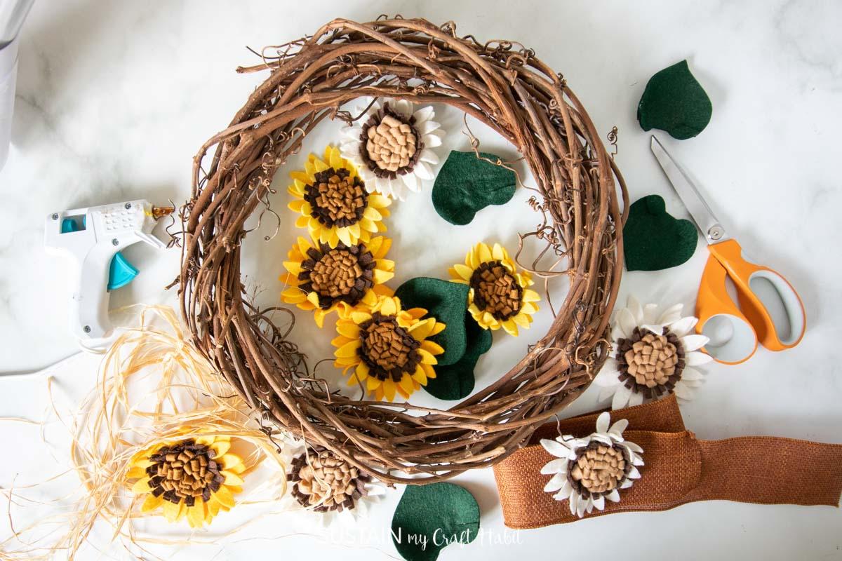 Materials needed to make a felt sunflower wreath including a grapevine wreath, felt flowers, scissors, ribbon and hot glue.