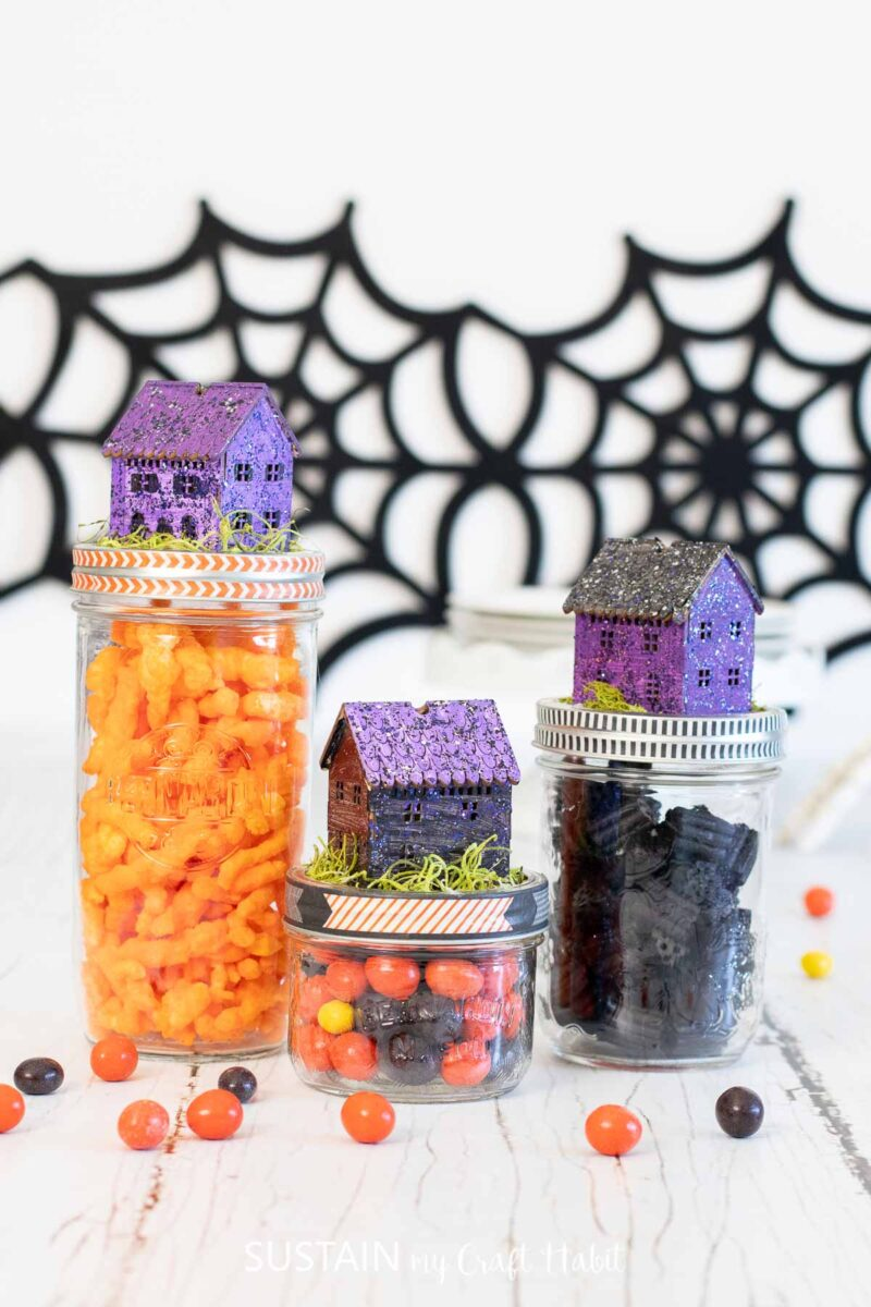 Candy filled mason jars with Halloween jar topper houses.