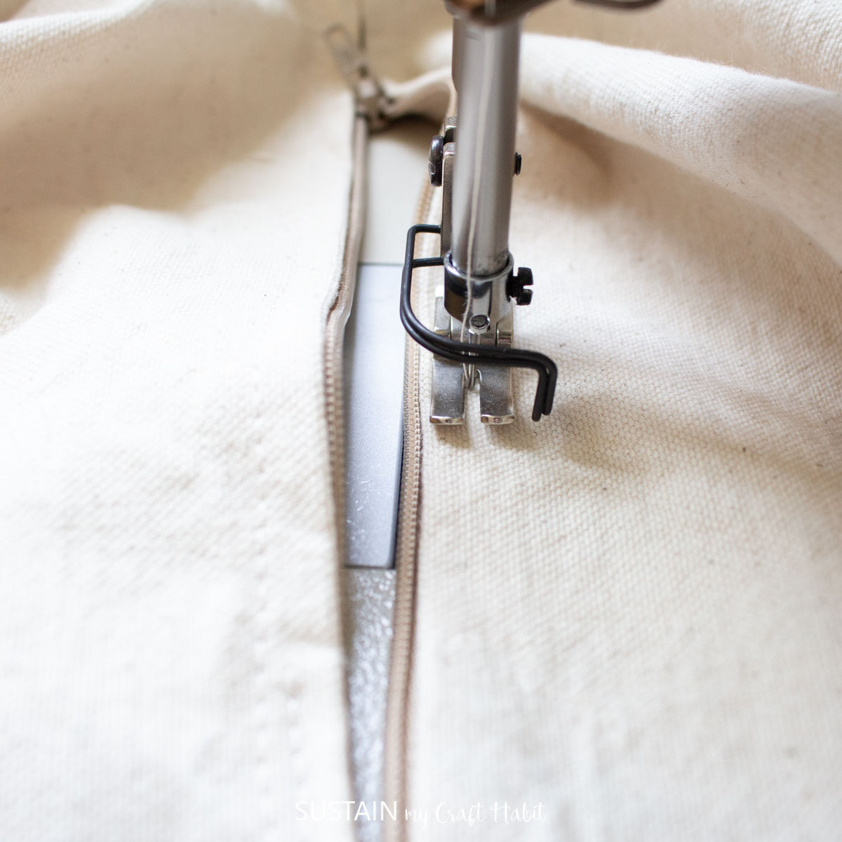 Sewing the zipper through all layers for the fabric canvas.