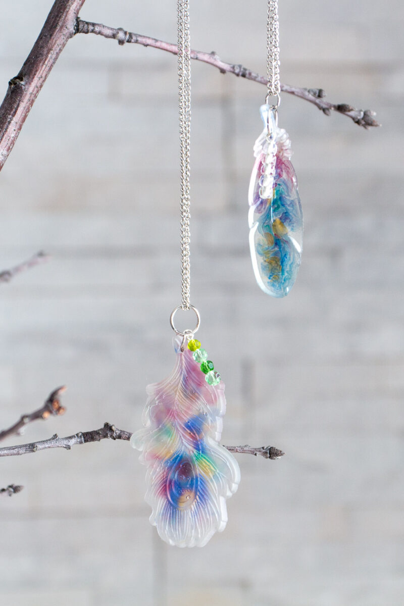 Resin feather pendants hanging from a branch.